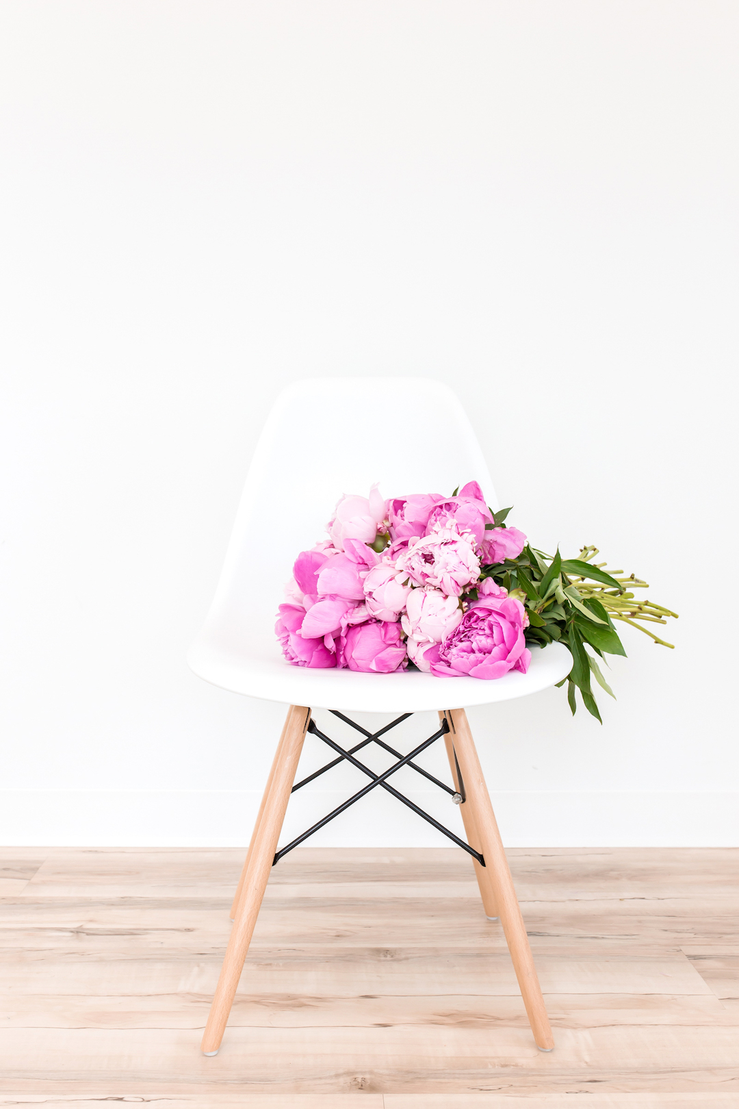 A bouquet of peonies on a modern white chair in front of a white wall and wooden floor