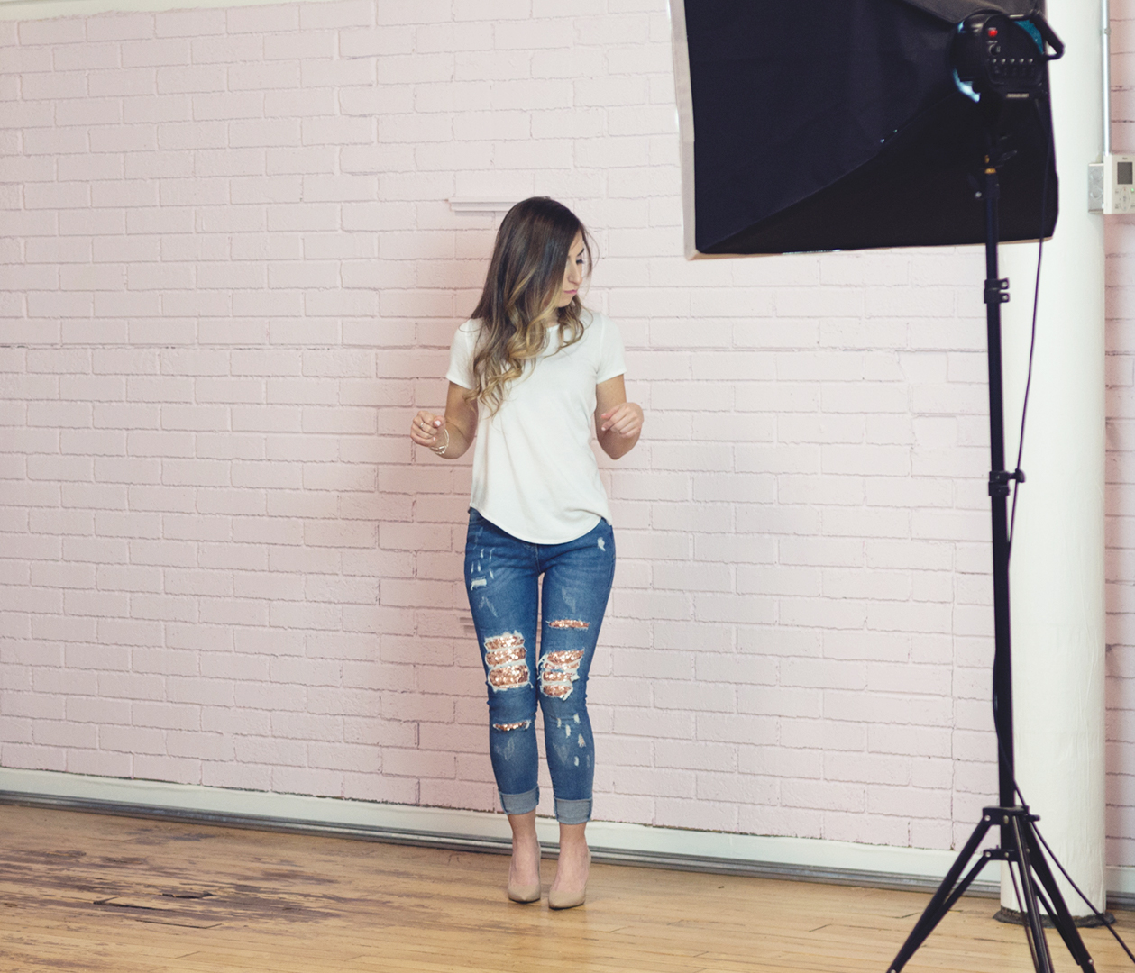 Tanya Conner-Green dancing in front of a pink brick wall with a photography studio light in the foreground